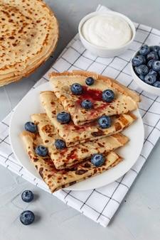ブルーベリーとサワークリームと白い市松模様のナプキンのプレートに薄いパンケーキ。上面図。
