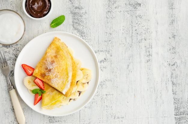 초콜릿 크림, 바나나 및 딸기가 들어간 얇은 팬케이크 또는 크레페