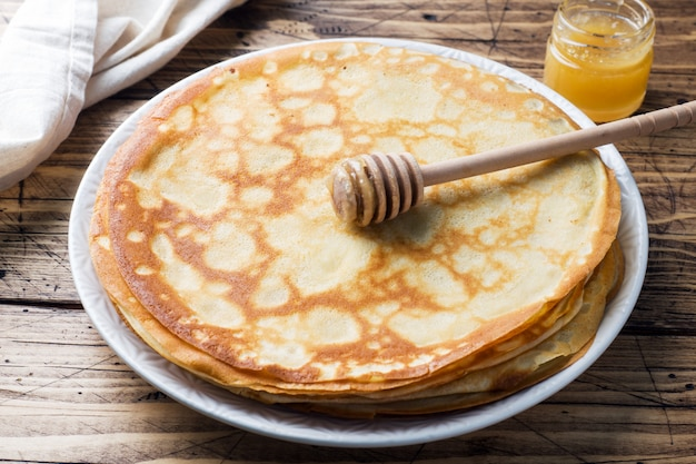 Thin pancakes on a plate with honey. wooden background.