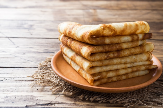 Thin pancakes stacked on a wooden background. copy space.
