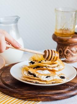 치즈, 자두, 사워 크림으로 속을 채운 얇은 팬케이크, 꿀 추가, 손, 아침 식사