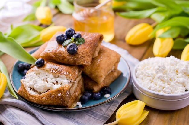 Тонкие блинчики с творогом и клубникой. концепция здорового традиционного завтрака. выпечка для традиционного русского карнавала весной, масленица. копировать пространство