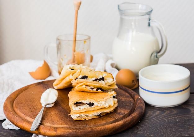 코티지 치즈, 자두, 꿀, 사워 크림을 넣은 얇은 팬케이크, 소박한 나무 판자