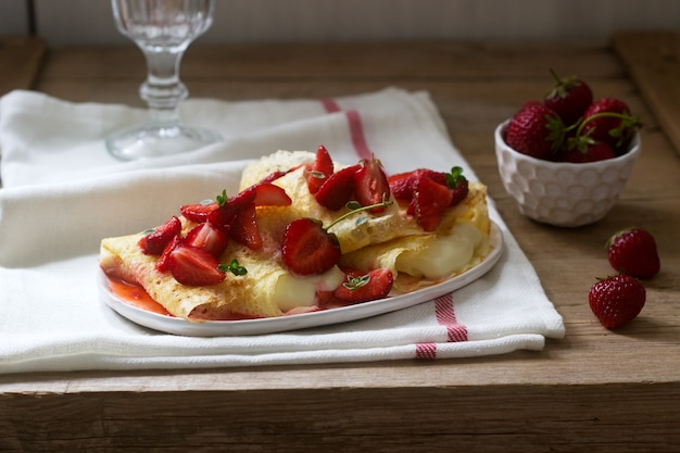 Thin pancakes with cream filling and strawberry sauce on a wooden table. rustic style.