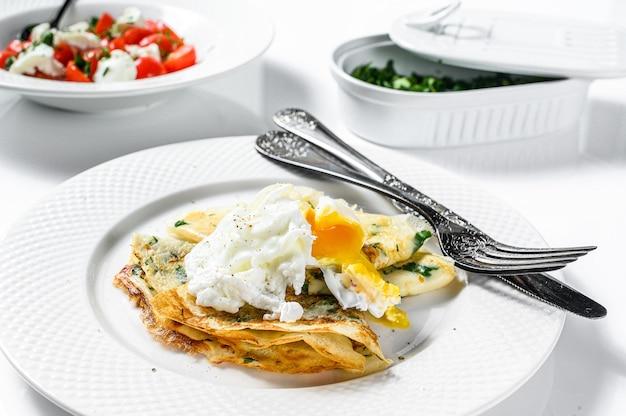 野菜とポーチドエッグの薄いパンケーキ。白色の背景。上面図。