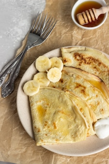 Thin pancakes with natural yogurt, honey and banana on a plate