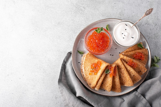 Thin pancakes with red caviar on a gray plate, top view