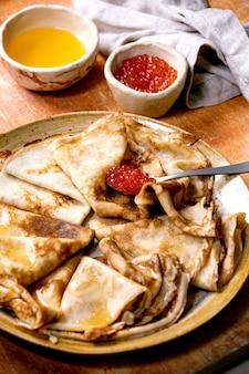 薄いパンサケのクレープシュゼットに、茶色の石の壁の上のセラミックプレートに赤キャビアと溶かしたバターを添えました。