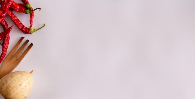 白い背景の上の木製のフォークと乾燥したカボチャと薄い赤唐辛子フラットレイコピースペース