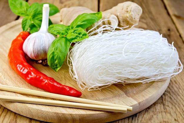 にんにく、赤唐辛子、生姜、バジル、木の板の背景に箸と細い米麺