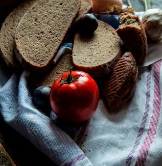 Тонко нарезанный черный хлеб вид сверху на белом полотенце с помидорами и сливой.