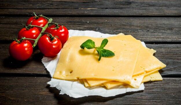 토마토와 민트 가지와 치즈의 얇은 조각. 나무 배경.