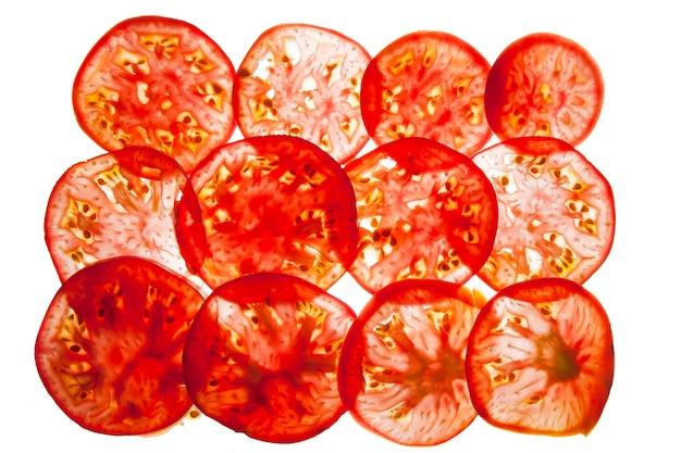 빛이 있는 밝은 배경에 붉은 익은 토마토의 얇은 조각