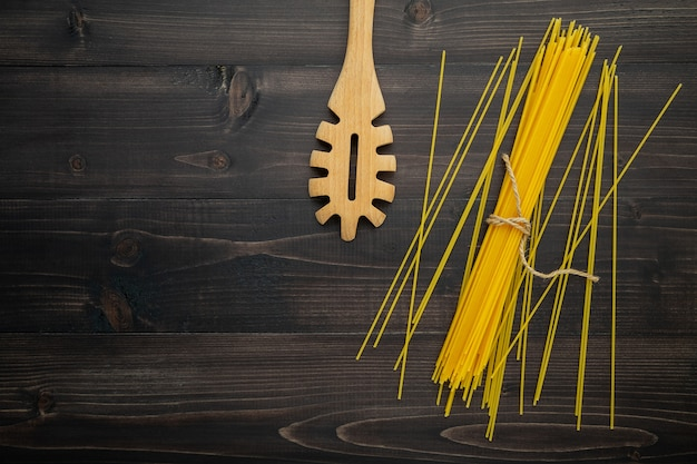 The thin spaghetti on black wooden background.