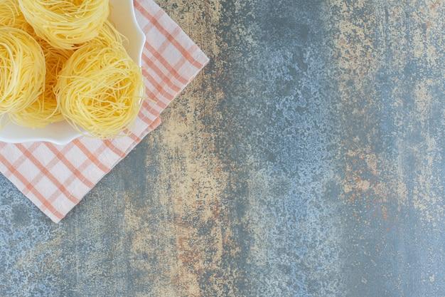 大理石の背景に、タオルの上のボウルに薄いスパゲッティ。