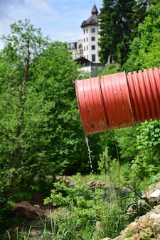 A thin stream of water flows from a red plastic sewer pipe against a blurred background of trees and a building