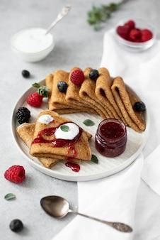 Тонкие сладкие блины со свежими ягодами и джемом на серой тарелке, крупный план