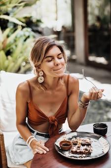 La donna sottile e abbronzata in reggiseno marrone e pantaloncini di jeans alla moda gode del gusto di waffle con panna, arachidi e sciroppo d'acero