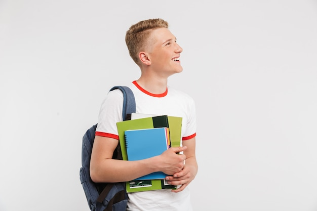 Thin teenage university or college student wearing backpack looking aside at copyspace while holding textbooks isolated on white