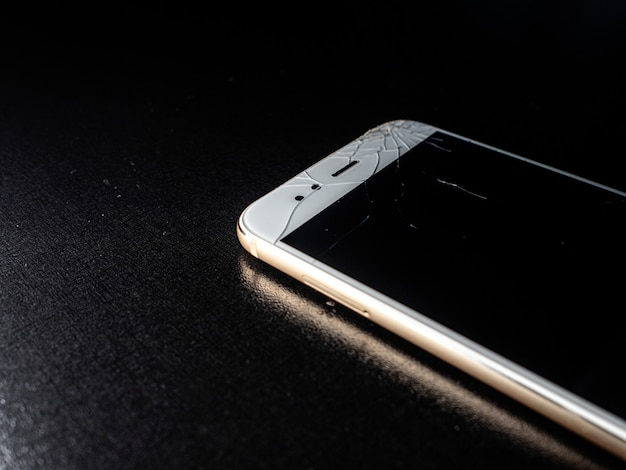 A thin white smartphone with a badly cracked screen, damage when falling.
