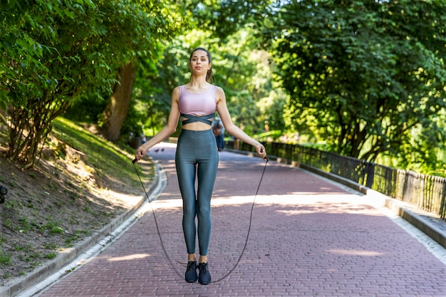 Thin woman is jumping rope on the park pathway