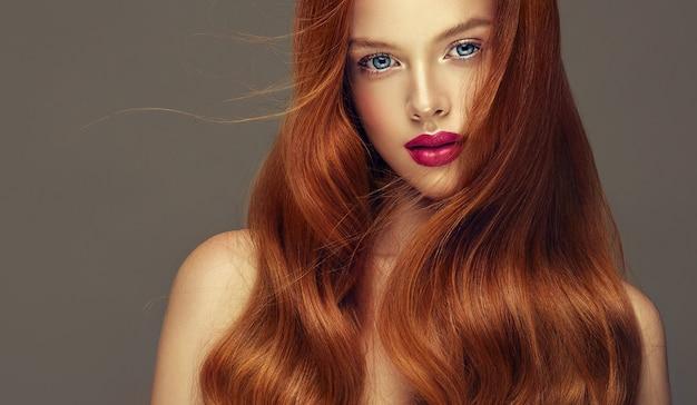 薄毛の髪の毛赤い光沢のある手入れの行き届いた長い髪の優れた波がきれいな女性の顔を囲んでいますぽっちゃりした唇に美しい青い目の桜の口紅の誠実な表情