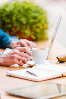 成功のためのもの。ノートパソコンで作業し、コーヒーのカップに手をつないで若い男のクローズアップ