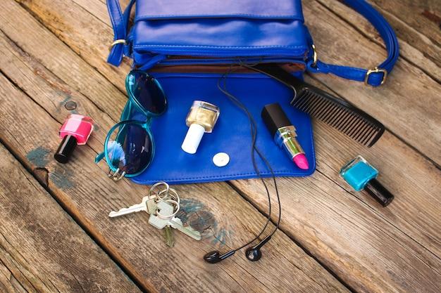 Вещи из открытого дамского кошелька. косметика и женские аксессуары выпали из синей сумочки.