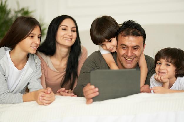 디지털 태블릿을 사용하여 귀여운 어린 아이들과 함께 행복한 라틴 가족