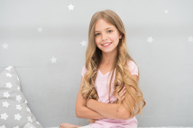 Things you shouldnt do at night if you want healthier hair. how to style hair before go to bed. girl with long curly hair grey background. hair care tips. easy way keep nice hairstyle.