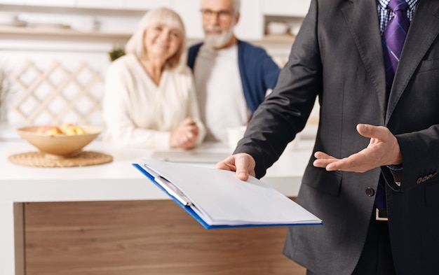 今日のあなたの健康について考えてください。自信を持って経験豊富な熟練した社会保障顧問が働いており、高齢のクライアントのカップルの隣で契約を提示しています