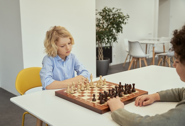 Think before you act thoughtful little caucasian boy playing chess with his friend sitting together