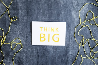 Think big text on white paper over the yellow thread on blackboard