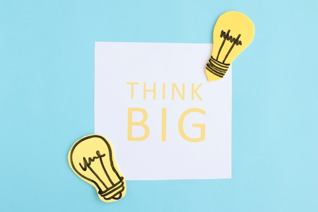 Think big text on white paper with light bulbs on blue background