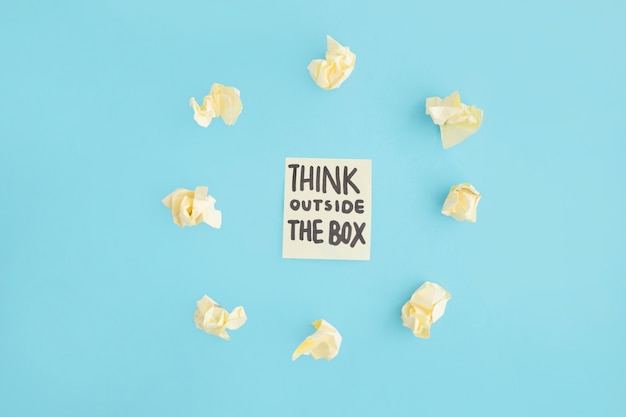 Think outside the box text on adhesive note surrounded with yellow crumpled paper over the blue backdrop