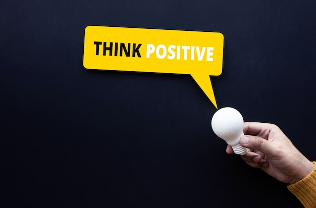 Think positive and creativity concepts with text and lightbulb on person hand.