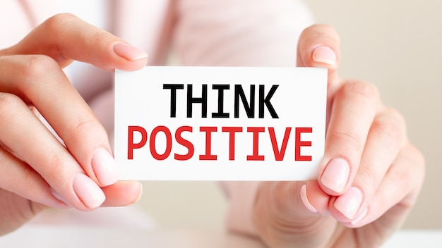 Think positive is written on a white business card in a woman's hands
