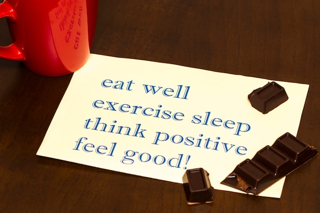 Think positively , exercise, eat well, sleep - concept feel good - handwriting on a sheet of paper