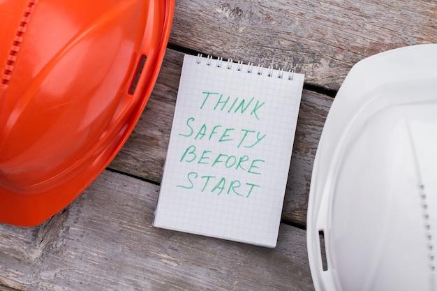 Подумайте о безопасности, прежде чем начинать. шлемы строителей конструктора на деревянном столе. плоский вид сверху.