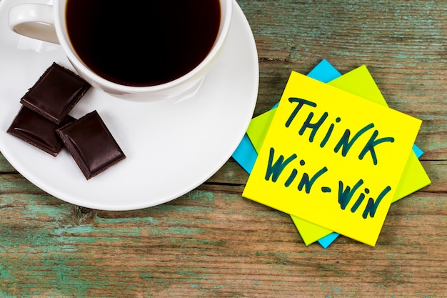 Think win-win concept - handwriting on a sticky note  with a cup of coffee and chocolate.