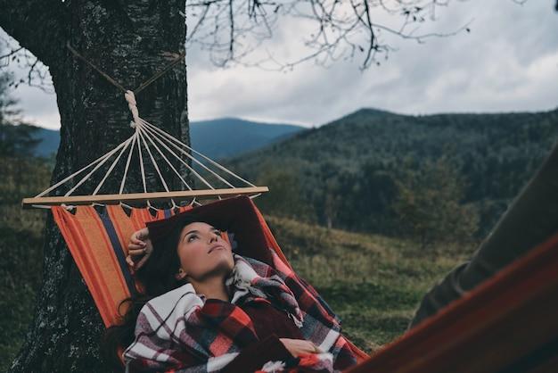 考えて...木の下の谷でリラックスしながらハンモックに横たわっている美しい若い女性