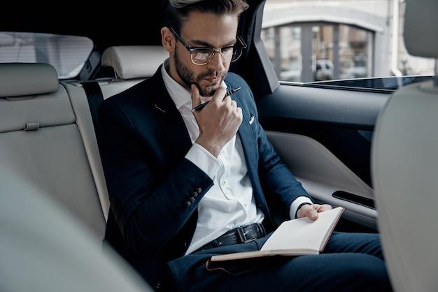 ビジネスについて考える。車の中に座っている間、手帳に何かを書き留めるスーツを着たハンサムな若い男