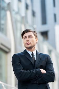 Думая о бизнес-решениях. задумчивый молодой человек в строгой одежде, скрестив руки на груди и глядя в сторону
