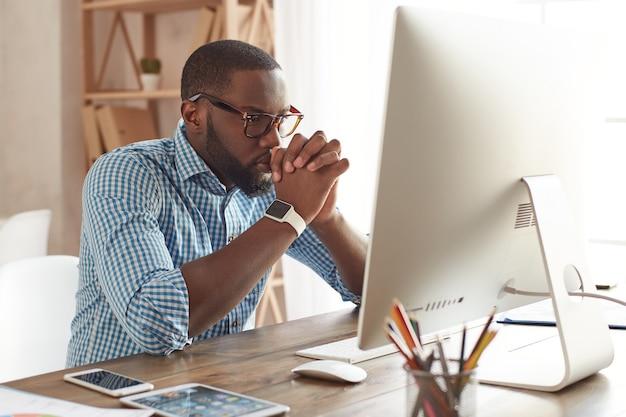 컴퓨터 화면을 보고 있는 안경을 쓴 사려 깊은 젊은 아프리카계 미국인 남자에 대해 생각