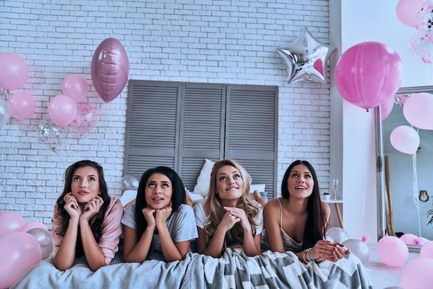 에 대해 생각? 잠옷을 입은 4명의 아름다운 젊은 여성이 침대에 누워 멀리 바라보고 있다