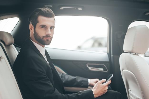 Думаю о новых возможностях. уверенный молодой бизнесмен, устанавливающий свой смартфон и смотрящий в камеру, сидя в машине