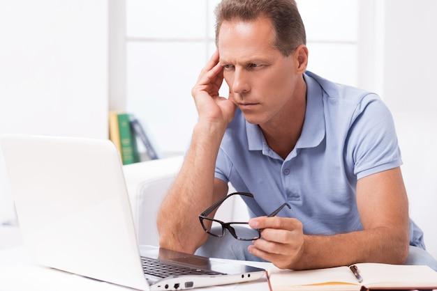 解決策を考えています。ノートパソコンを見て、自宅のソファに座って手で頭に触れる思いやりのある成熟した男