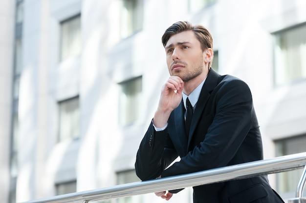 Думаю о решениях. вид сбоку на молодого человека в строгой одежде, держащего руку за подбородок и смотрящего в сторону, стоя на открытом воздухе