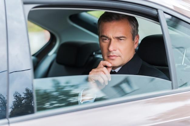 ソリューションについて考える。あごに手を握り、車の後部座席に座って目をそらしている思いやりのある成熟したビジネスマン