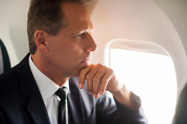 ソリューションについて考える。飛行機の彼の席に座っている思いやりのある成熟したビジネスマン
